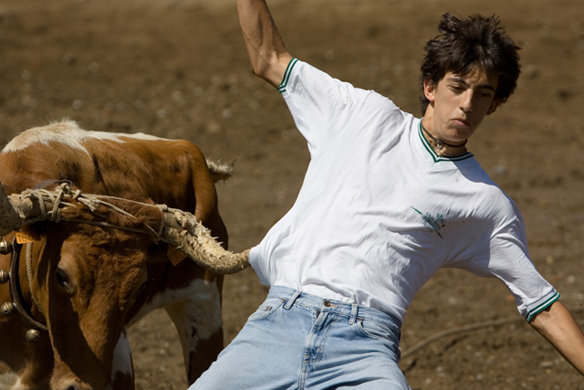 "A bull hooks the t-shirt of a ""cuadrilla"" with its horn as he runs."