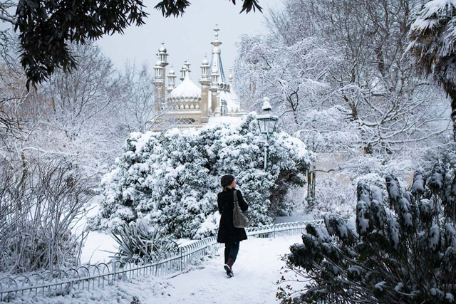 Young woman walking through snow, Royal Pavilion, Brighton (Telegraph, Times)
