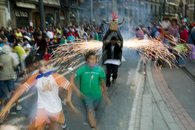 Children enjoy fleeing from the 'Bull of Fire' during Aste Nagusia, fiesta, Bilbao.