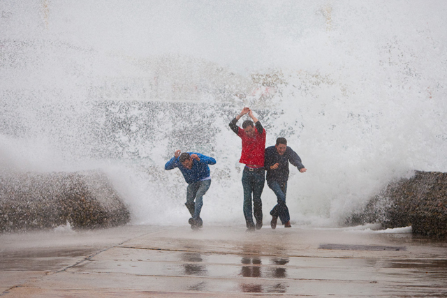 Three men failing to dodge a breaking wave, Brighton (Daily Mirror)